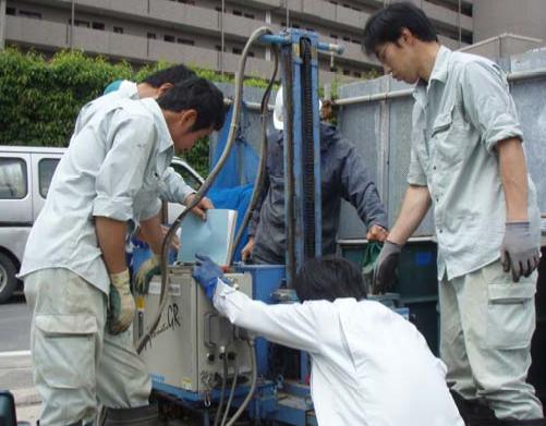 資材置場で仲間と新しい機械の講習をうける